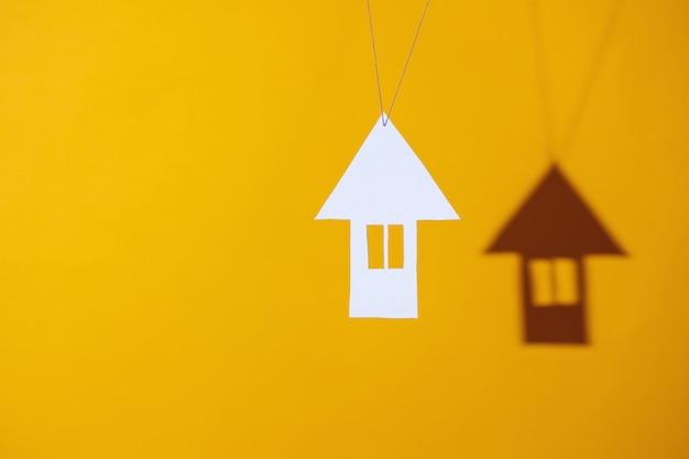 Piccola casa di cartone getta un'ombra su uno sfondo colorato luminoso