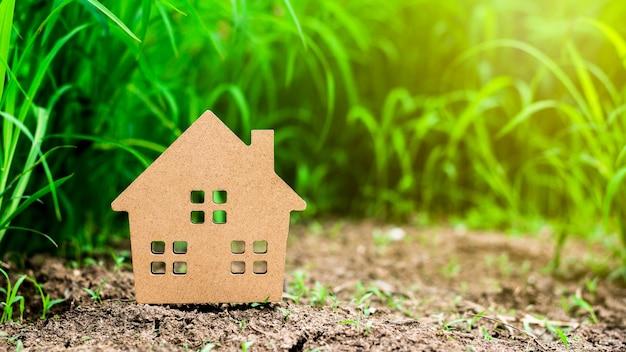 Piccola casa di modello nel campo di erba verde.
