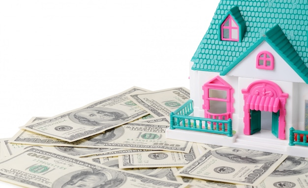 Piccola casa giocattolo in piedi su cento banconote in dollari