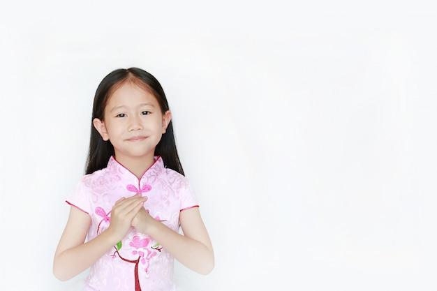 Piccola celebrazione asiatica sorridente di gesto di saluto della ragazza per il nuovo anno cinese.