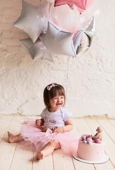 Piccola festa di compleanno affascinante bambino in abito rosa si siede sulla sedia