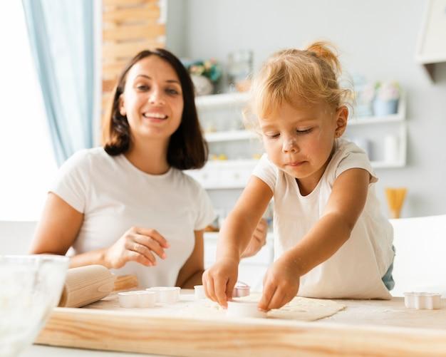 Piccola figlia e madre che preparano i biscotti