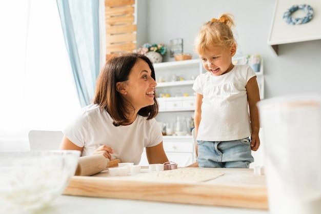 Piccola figlia e madre felici che cucinano insieme