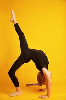 Piccola ginnasta che balla i movimenti acrobatici su fondo giallo, scuola di ginnastica ritmica, infanzia sportiva felice