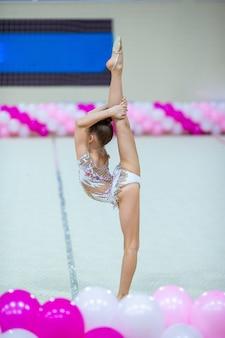 Piccola ginnasta che si allena sul tappeto e pronta per le competizioni