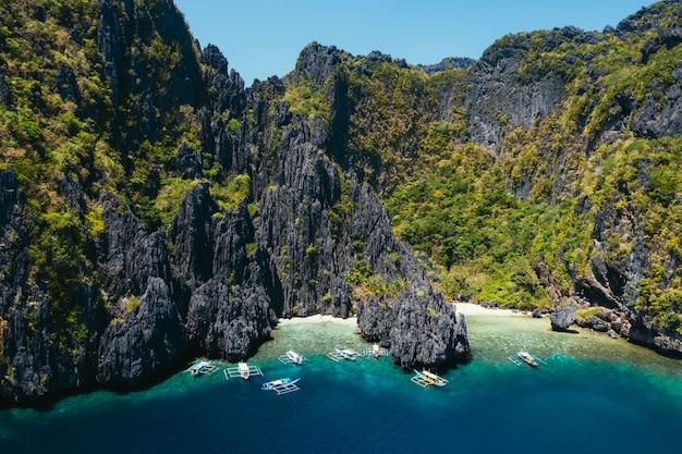 Piccola laguna a el nido. la gente che cammina sulla sabbia bianca, con la giungla tropicale. concetto di viaggio e natura