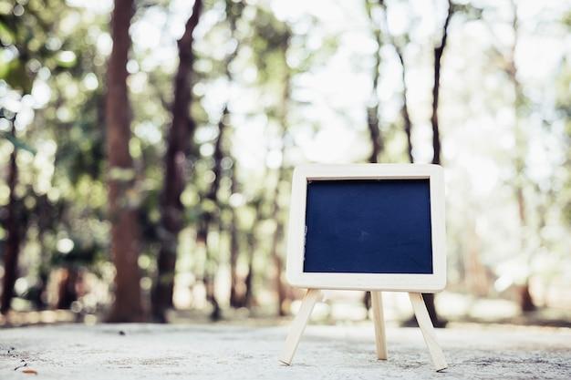 Piccola lavagna a-frame con spazio vuoto per testo o messaggio sul tavolo in legno rustico in mattinata