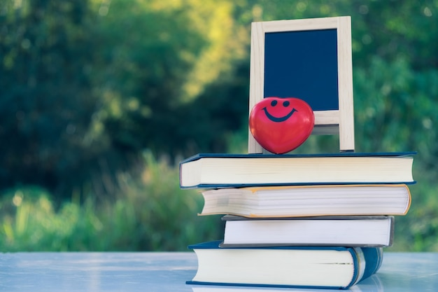 Piccola lavagna a-frame e sorriso cuore rosso sulla pila di libri con spazio vuoto per testo o messaggio sulla tavola di legno rustico in mattinata