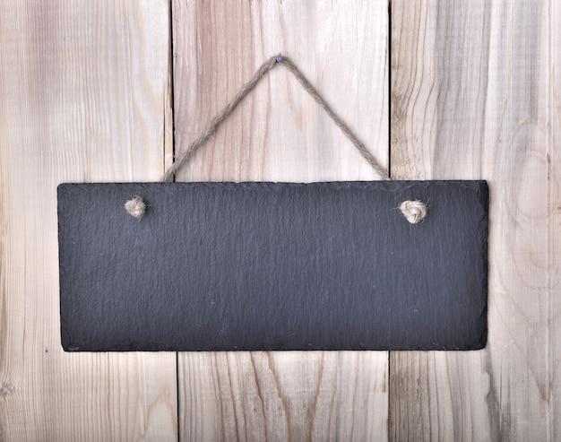 Piccola lavagna appesa a una corda su una tavola di legno