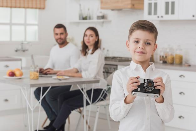 Piccola macchina fotografica della tenuta del giovane ragazzo