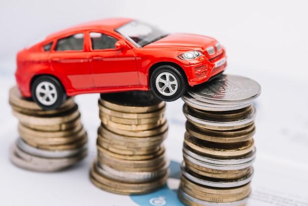Piccola macchina rossa sopra la pila di monete in aumento