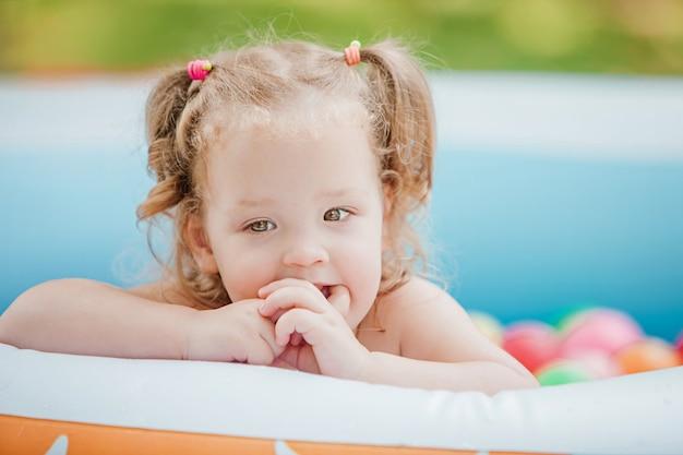 Piccola neonata che gioca con i giocattoli nello stagno gonfiabile nel giorno soleggiato di estate