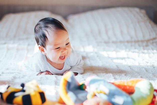 Piccola neonata di tre mesi sveglia, giocante a casa a letto in camera da letto