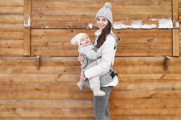 Piccola neonata e sua madre babywearing nel trasportatore di ergo nel fondo di legno di inverno
