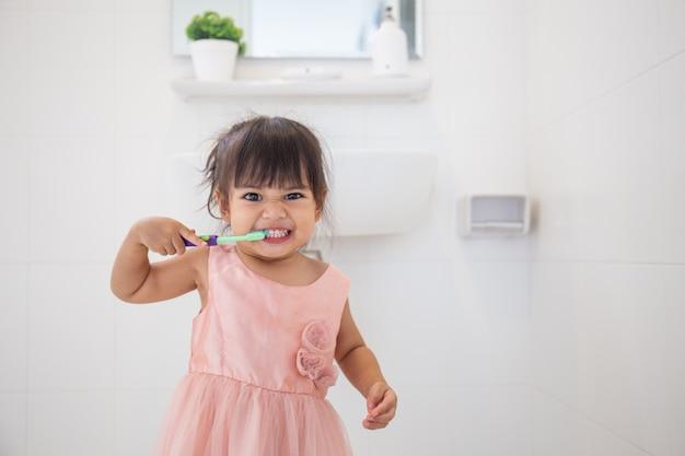 Piccola neonata sveglia che pulisce i suoi denti con lo spazzolino da denti nel bagno