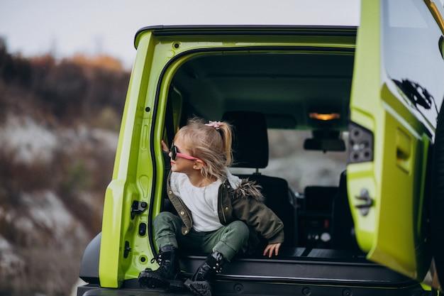 Piccola neonata sveglia che si siede nella parte posteriore della macchina