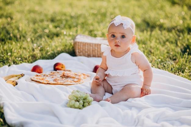 Piccola neonata sveglia che si siede sulla coperta nel parco