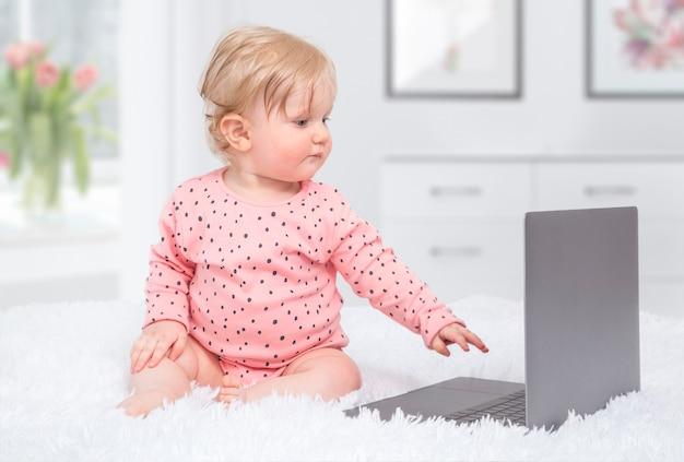 Piccola neonata sveglia con il computer portatile nella camera da letto del genitore