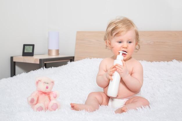 Piccola neonata sveglia con la bottiglia di olio per bambini nella camera da letto del genitore.
