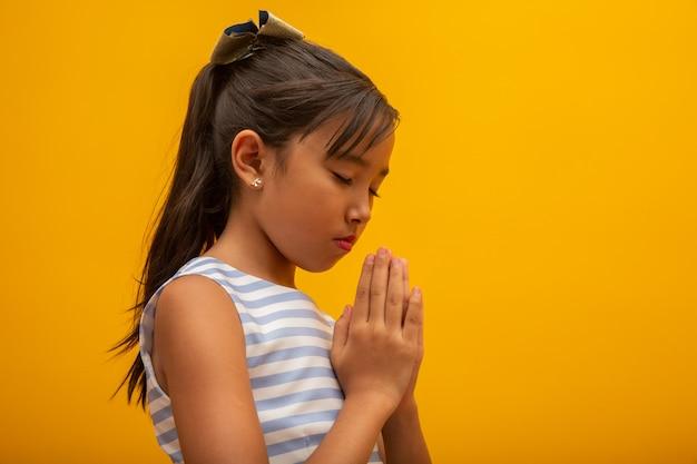 Piccola preghiera asiatica della mano della ragazza