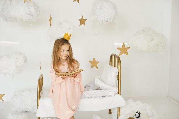 Piccola principessa con una bacchetta magica su un letto in una nuvola su uno sfondo bianco