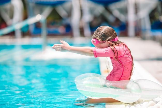 Piccola ragazza adorabile attiva nella piscina all'aperto pronta a nuotare