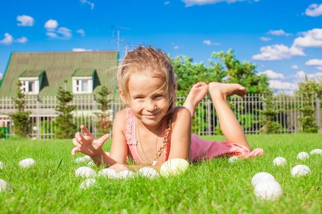 Piccola ragazza adorabile che gioca con le uova di pasqua bianche nell'iarda