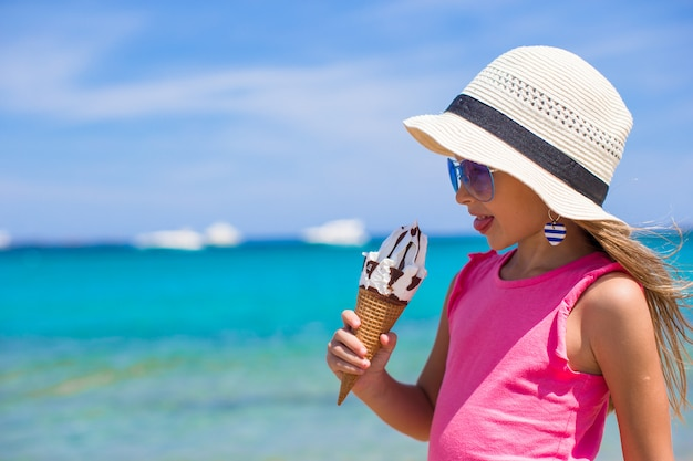 Piccola ragazza adorabile che mangia il gelato sulla spiaggia tropicale