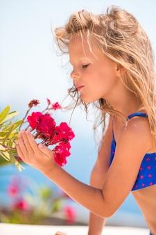 Piccola ragazza adorabile che odora i fiori variopinti al giorno di estate