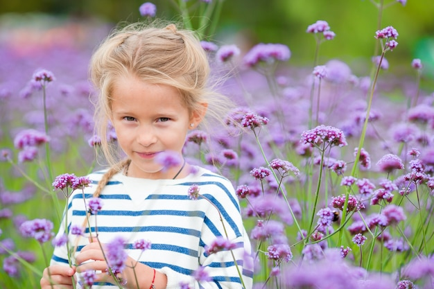 Piccola ragazza adorabile che odora i fiori variopinti all'aperto