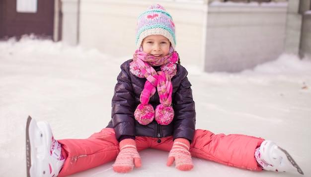 Piccola ragazza adorabile che si siede sul ghiaccio dopo la caduta
