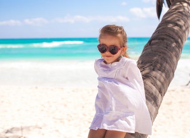 Piccola ragazza adorabile che si siede sulla palma alla spiaggia caraibica perfetta