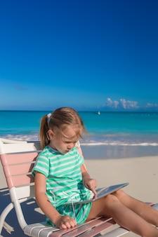 Piccola ragazza adorabile con il computer portatile sulla spiaggia durante le vacanze estive