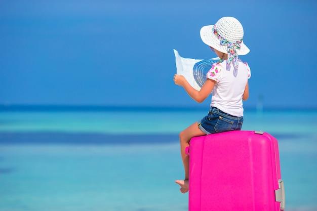Piccola ragazza adorabile con la grande valigia e mappa rosa dell'isola sulla spiaggia bianca