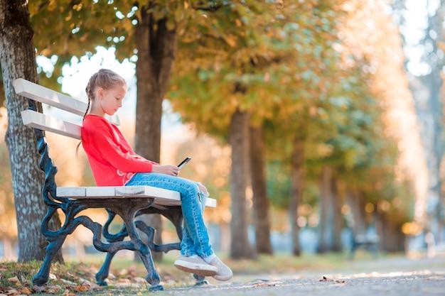 Piccola ragazza adorabile con smartphone in autunno. scherzi divertendosi al giorno soleggiato caldo di autunno all'aperto