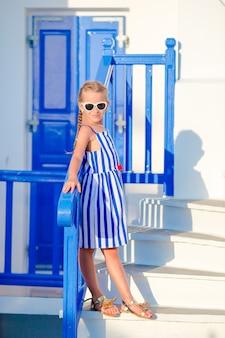 Piccola ragazza adorabile in vestito all'aperto in vecchie strade un mykonos. scherzi alla via del villaggio tradizionale greco tipico con le pareti bianche e le porte variopinte sull'isola di mykonos, in grecia
