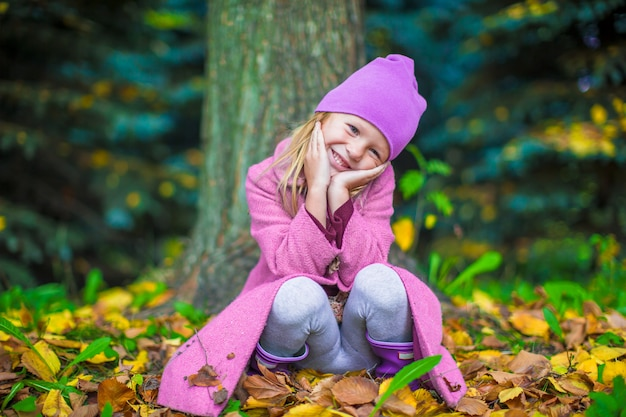Piccola ragazza adorabile nel parco di autunno il giorno soleggiato dell'autunno