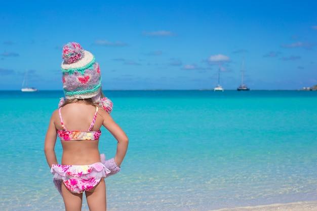 Piccola ragazza adorabile sveglia sulla spiaggia tropicale