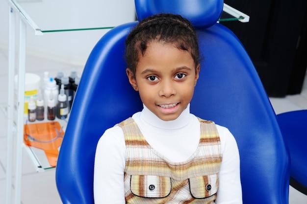 Piccola ragazza africana con la pelle scura in odontoiatria