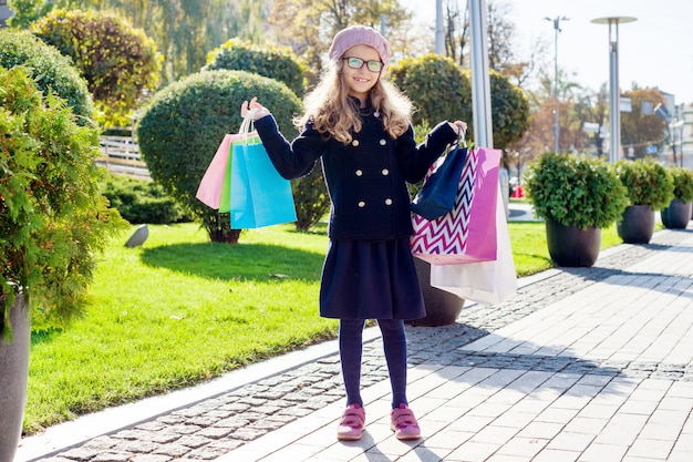 Piccola ragazza alla moda tenendo i sacchetti della spesa