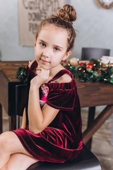 Piccola ragazza allegra nella decorazione di natale con tè a casa accogliente con le luci variopinte del nuovo anno