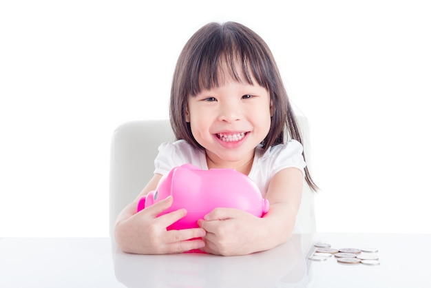 Piccola ragazza asiatica che abbraccia banca piggy dentellare sopra priorità bassa bianca