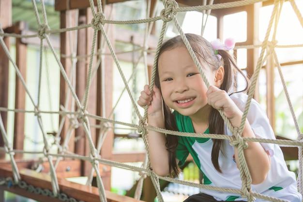 Piccola ragazza asiatica che gioca e sorride nel cortile della scuola