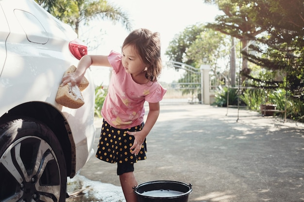 Piccola ragazza asiatica che lava un'automobile a casa