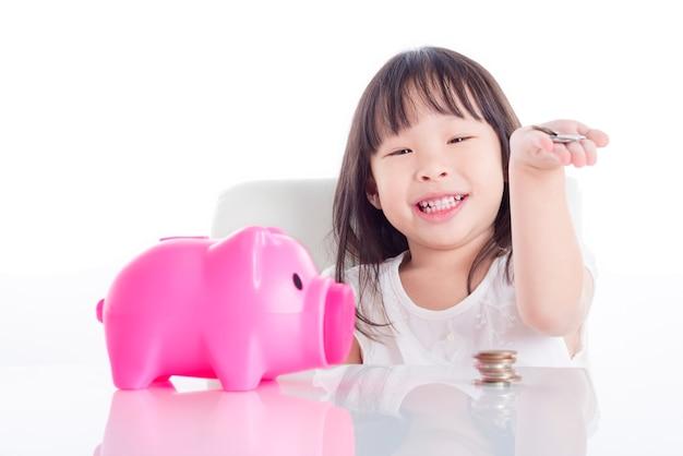 Piccola ragazza asiatica che mostra i suoi soldi con la banca piggy dentellare sopra priorità bassa bianca