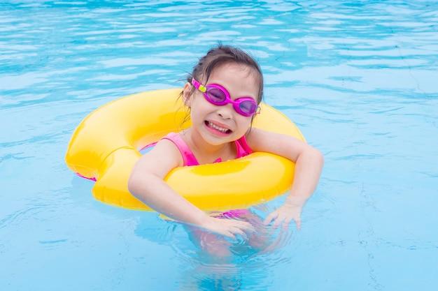 Piccola ragazza asiatica che nuota con l'anello in piscina
