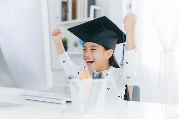Piccola ragazza asiatica che porta il cappello laureato che fa i compiti e sorride con felicità per successo di istruzione.