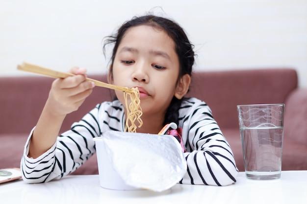 Piccola ragazza asiatica che si siede alla tavola bianca per mangiare tagliatella istantanea