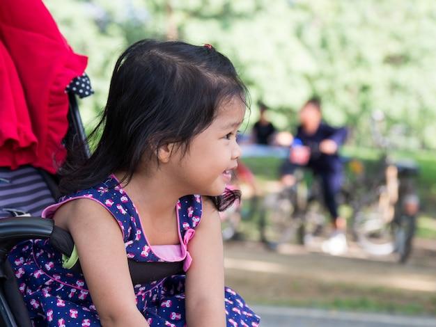 Piccola ragazza asiatica che si siede in un passeggiatore al parco pubblico.
