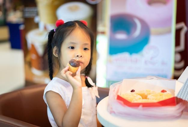Piccola ragazza asiatica che si siede sulla sedia con la tenuta e il cibo delle ciambelle